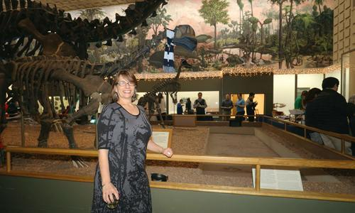 Vivian Irish at Peabody Museum in front of Main Hall dinosaurs