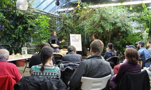 people attending a lecture in a greenhouse
